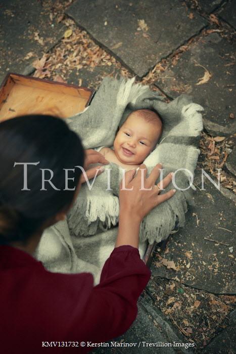 Kerstin Marinov WOMAN FINDING BABY IN SUITCASE WITH BLANKET Children