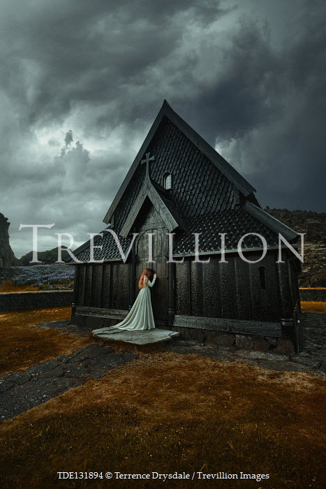 Terrence Drysdale WOMAN OUTSIDE CHURCH IN STORMY COUNTRYSIDE Women