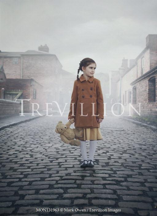 Mark Owen LITTLE GIRL CARRYING TEDDY ON COBBLED STREET Children