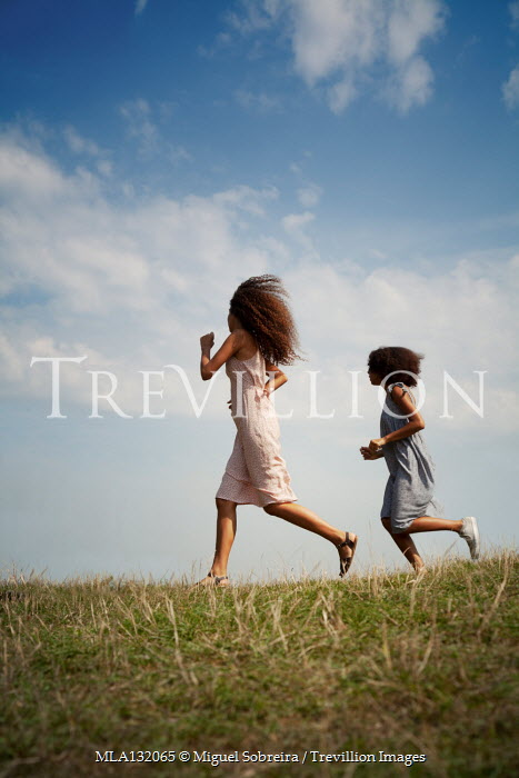 Miguel Sobreira TWO GIRLS RUNNING IN FIELD WITH BLUE SKY Women