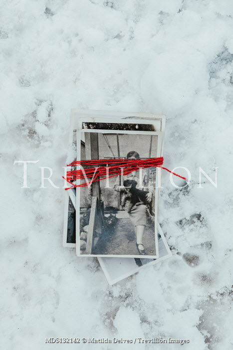 Matilda Delves PHOTOGRAPHS TIED WITH RED STRING LYING IN SNOW Miscellaneous Objects