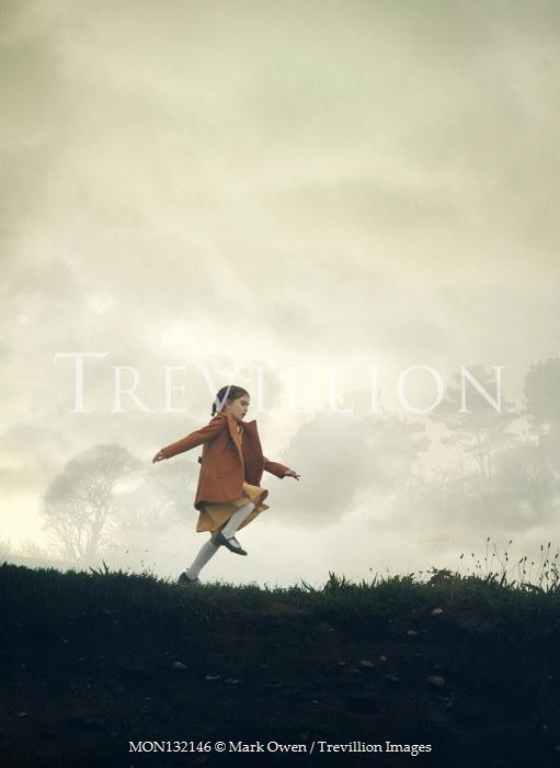 Mark Owen LITTLE GIRL WITH COAT RUNNING IN FOGGY FIELD Children