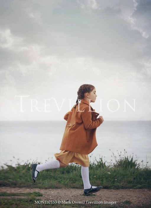 Mark Owen LITTLE GIRL WITH COAT RUNNING BY SEA Children