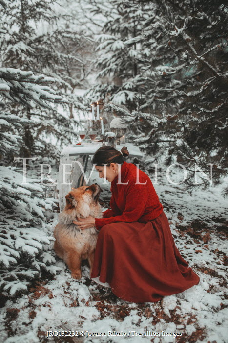 Jovana Rikalo WOMAN AND DOG SITTING BY TABLE IN SNOW Women