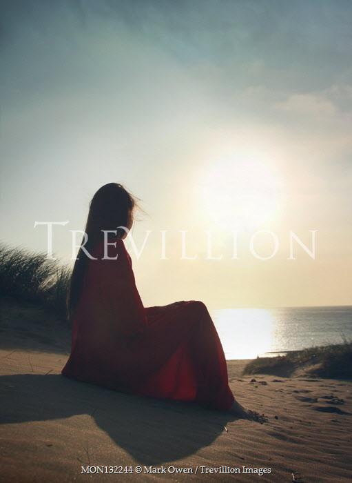 Mark Owen WOMAN SITTING ON BEACH WATCHING SUNSET Women