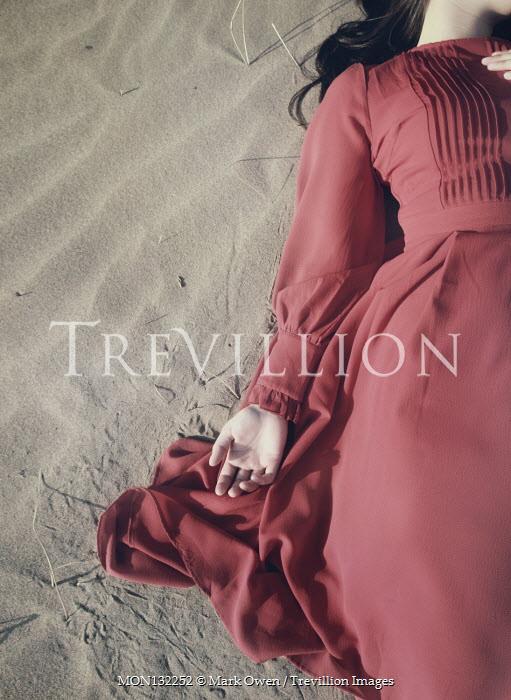 Mark Owen BRUNETTE WOMAN IN RED DRESS LYING ON SAND Women