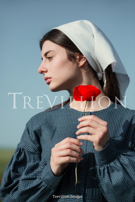 Magdalena Russocka close up of historical maid with poppy standing in field