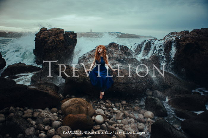 Katerina Klio WOMAN WITH RED HAIR SITTING ON ROCKS BY SEA Women