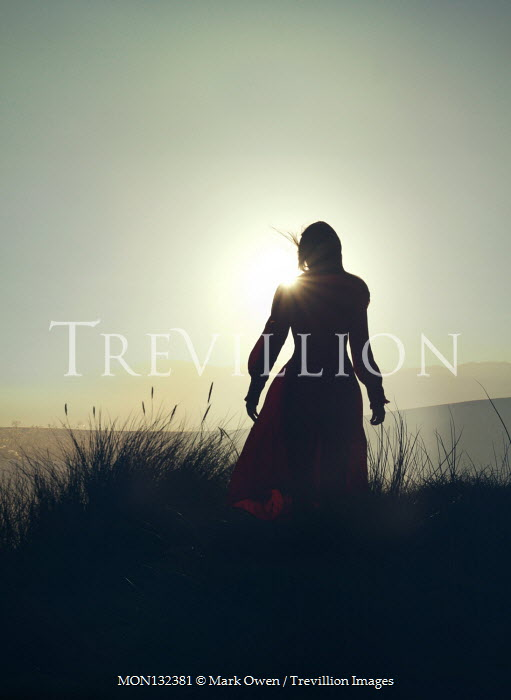 Mark Owen WOMAN STANDING IN DUNES AT SUNSET Women
