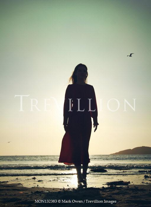 Mark Owen WOMAN IN SHADOW ON BEACH AT SUNSET Women