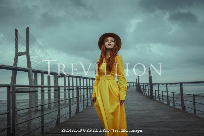 Katerina Klio WOMAN IN YELLOW WITH HAT STANDING BY BRIDGE Women