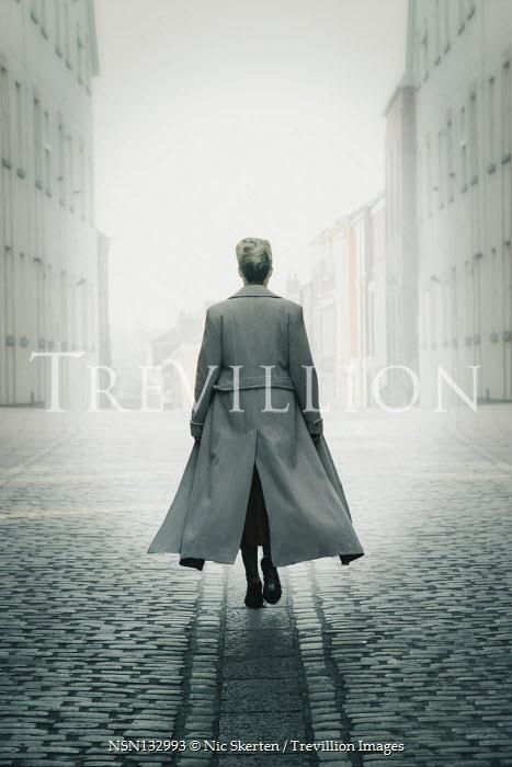Nic Skerten WOMAN IN COAT WALKING IN FOGGY CITY Women