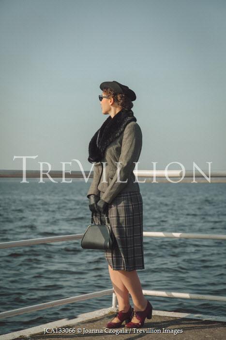 Joanna Czogala RETRO WOMAN STANDING BY RAILINGS WATCHING SEA Women