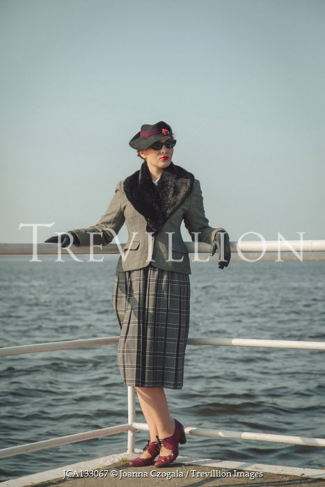 Joanna Czogala RETRO WOMAN BY RAILINGS WITH RIPPLED SEA Women