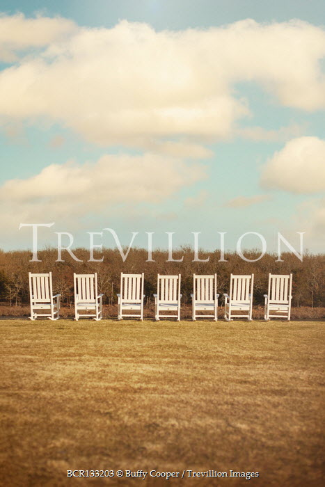 Buffy Cooper Rocking chairs in row under clouds