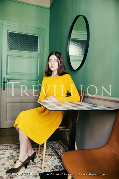 Krasimira Petrova Shishkova Young woman in yellow dress sitting at table