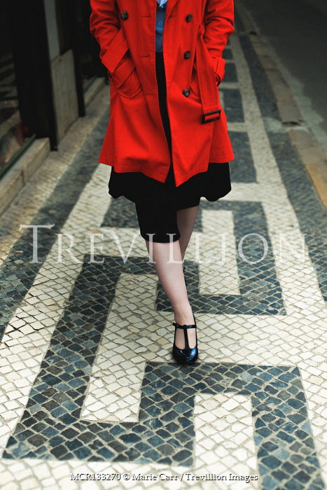 Marie Carr Woman in red coat walking on tiles