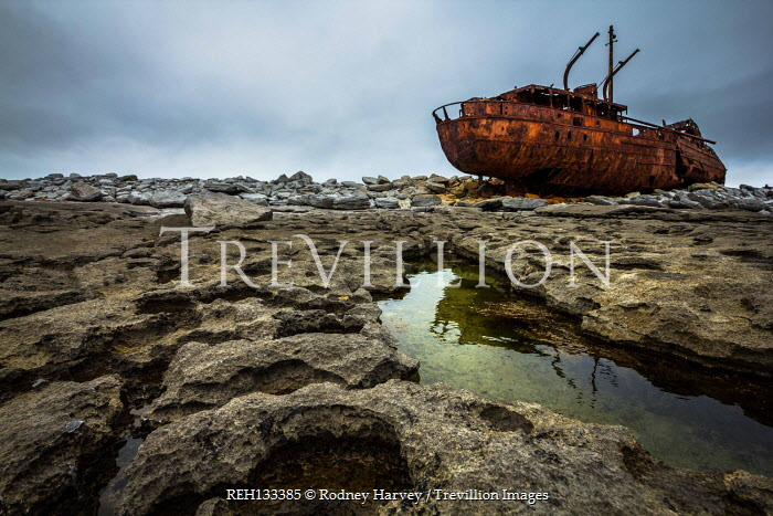 Rodney Harvey Rusted abandoned boat on rocks at coast