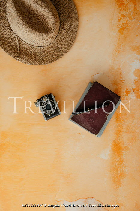 Angela Ward-Brown Journal, camera, and hat on orange table