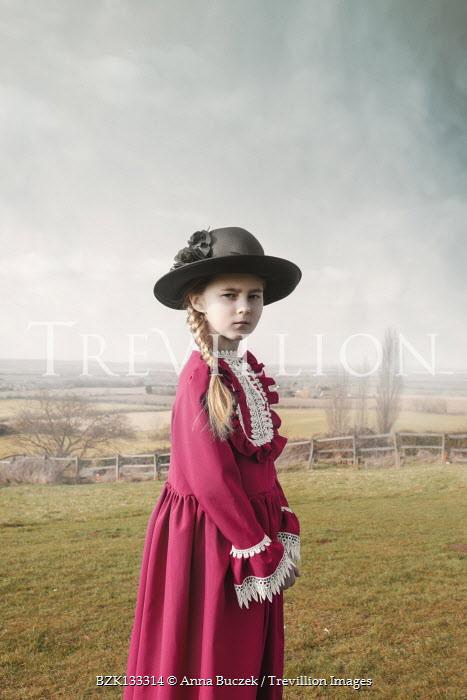 Anna Buczek Girl in Victorian hat and dress standing in field