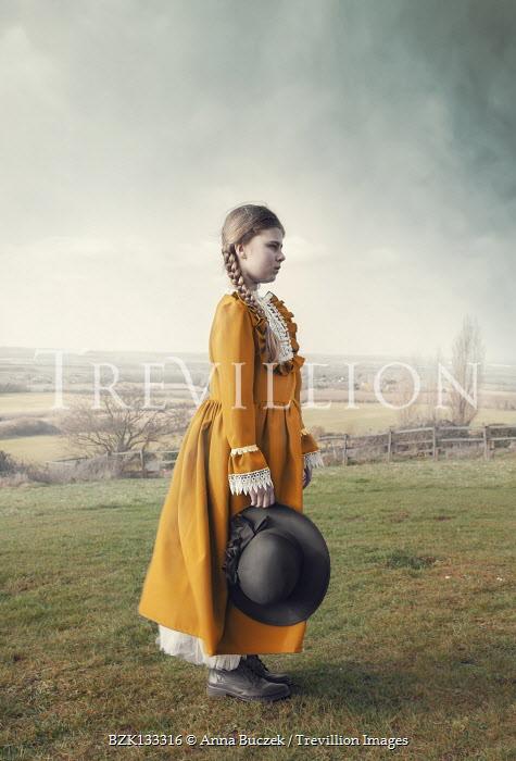 Anna Buczek Victorian girl in yellow dress standing in field