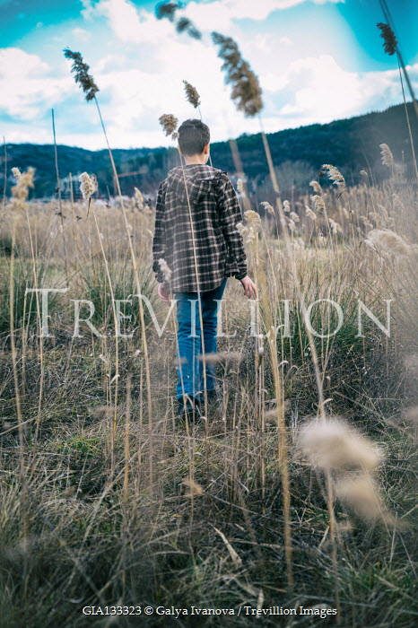 Galya Ivanova Boy in checked hoodie walking in field