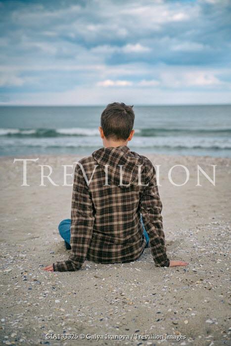 Galya Ivanova Boy in checked hoodie sitting on beach