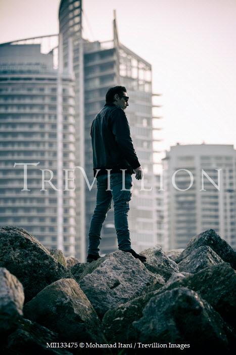 Mohamad Itani MAN STANDING ON ROCKS WITH HIGH RISE BUILDINGS Men
