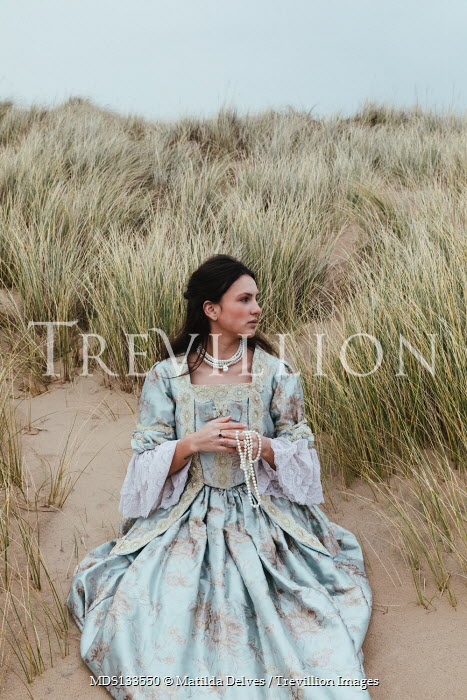Matilda Delves HISTORICAL WOMAN WITH JEWELLERY SITTING IN SAND DUNES Women