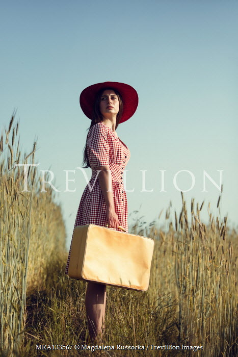 Magdalena Russocka young woman with hat and suitcase standing in field of rye