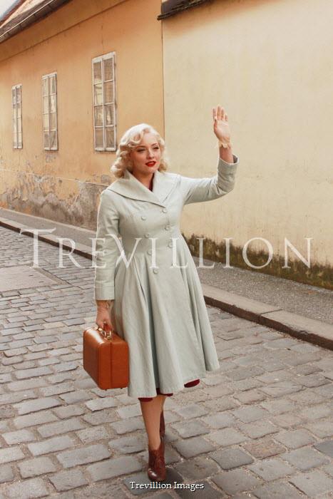 Jasenka Arbanas BLONDE WOMAN WAVING AND CARRYING CASE IN STREET