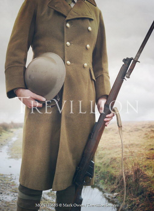 Mark Owen WWI SOLDIER HOLDING RIFLE AND HELMET OUTDOORS