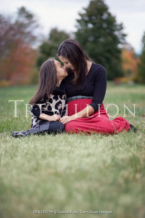 Susan Fox AFFECTIONATE MOTHER AND DAUGHTER SITTING IN COUNTRYSIDE