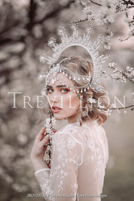 Jovana Rikalo BLONDE WOMAN WITH HEADDRESS BY TREE IN BLOSSOM