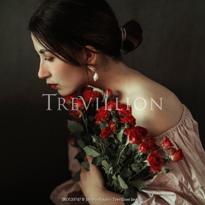 Jovana Rikalo WOMAN WITH DARK HAIR HOLDING RED ROSES