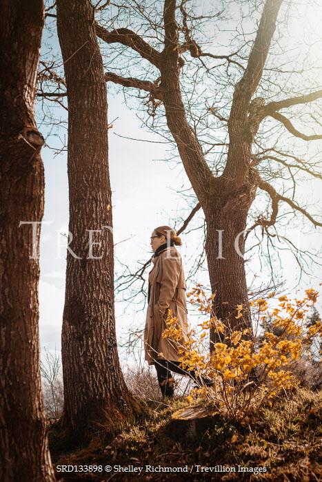 Shelley Richmond BLONDE WOMAN IN RAINCOAT WALKING OUTDOORS IN AUTUMN
