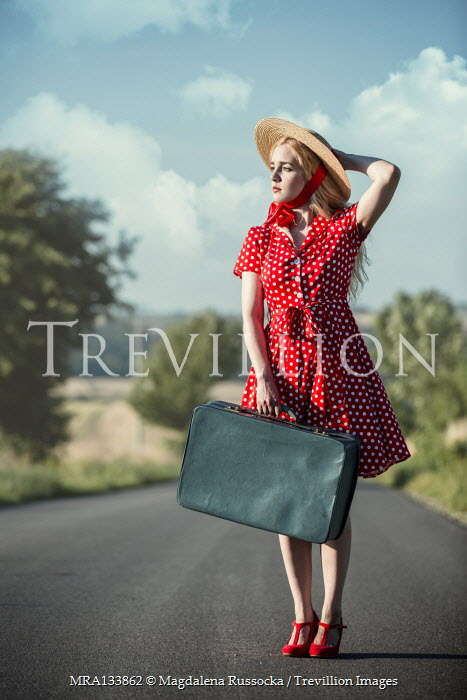 Magdalena Russocka young woman with straw hat and suitcase standing on country road