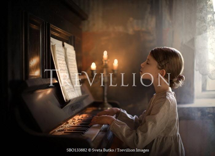Sveta Butko LITTLE GIRL PLAYING PIANO WITH GLOWING CANDELABRA