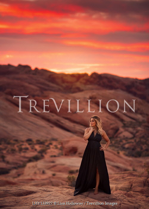 Lisa Holloway WOMAN IN GOWN STANDING IN DESERT AT SUNSET