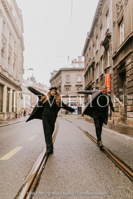 Muna Nazak COUPLE WALKING ON TRAM LINES IN CITY