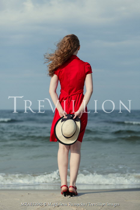 Magdalena Russocka woman in red dress holding hat standing on beach