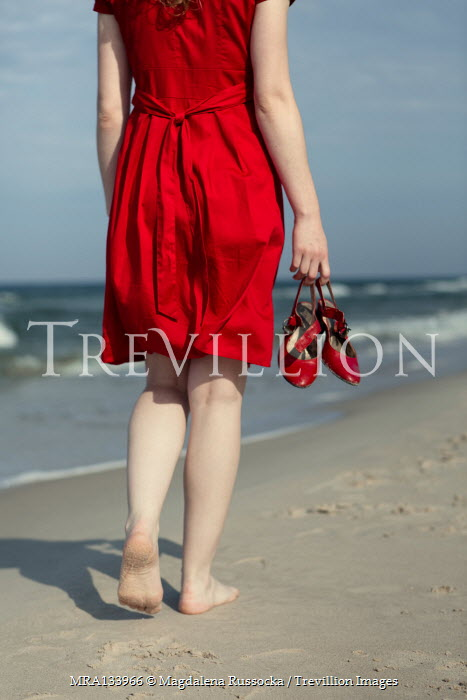 Magdalena Russocka barefoot woman in red dress walking on beach