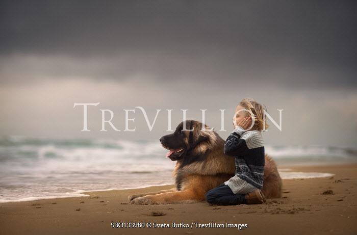 Sveta Butko LITTLE BOY SITTING ON SANDY BEACH WITH DOG
