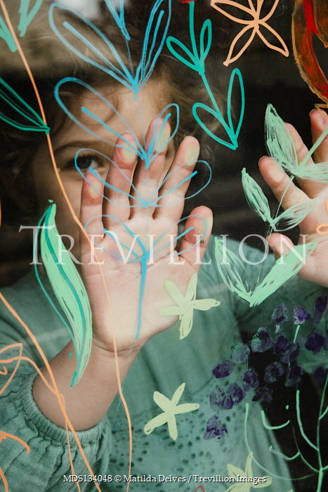 Matilda Delves LITTLE GIRL PRESSING HANDS ON PAINTED WINDOW