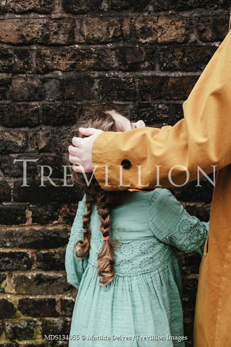 Matilda Delves MOTHER TOUCHING DAUGHTER'S HEAD BY BRICK WALL
