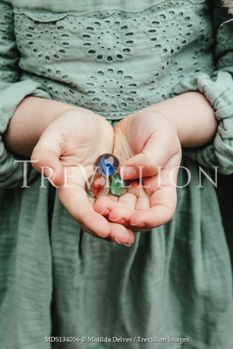 Matilda Delves HANDS OF LITTLE GIRL HOLDING MARBLES