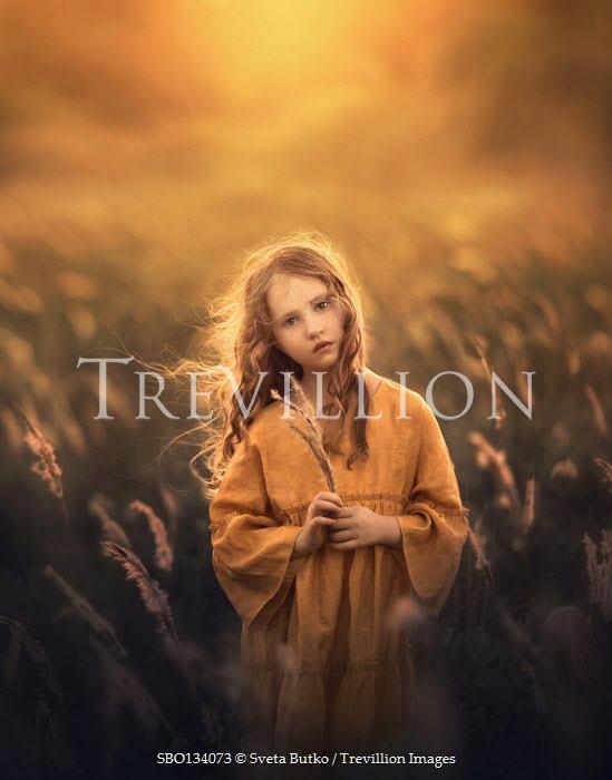 Sveta Butko SERIOUS LITTLE GIRL STANDING IN GOLDEN FIELD