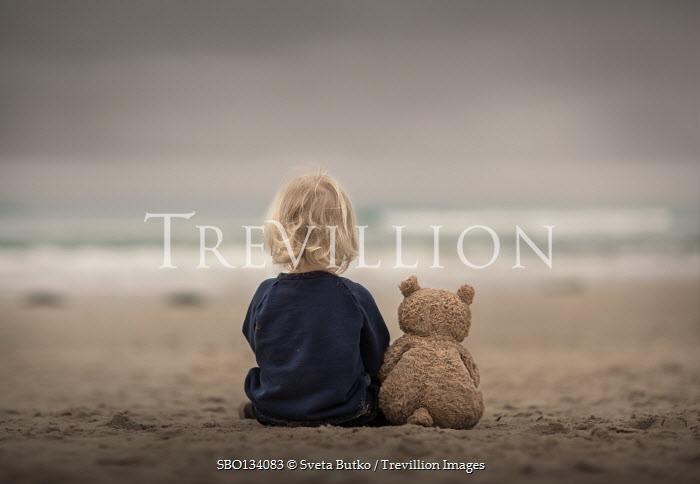 Sveta Butko LITTLE BLONDE CHILD SITTING ON BEACH WITH TEDDY