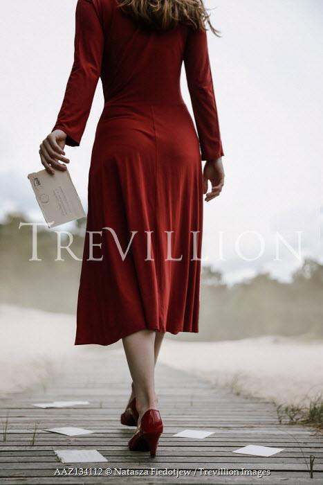 Natasza Fiedotjew woman walking away and dropping letters on boardwalk