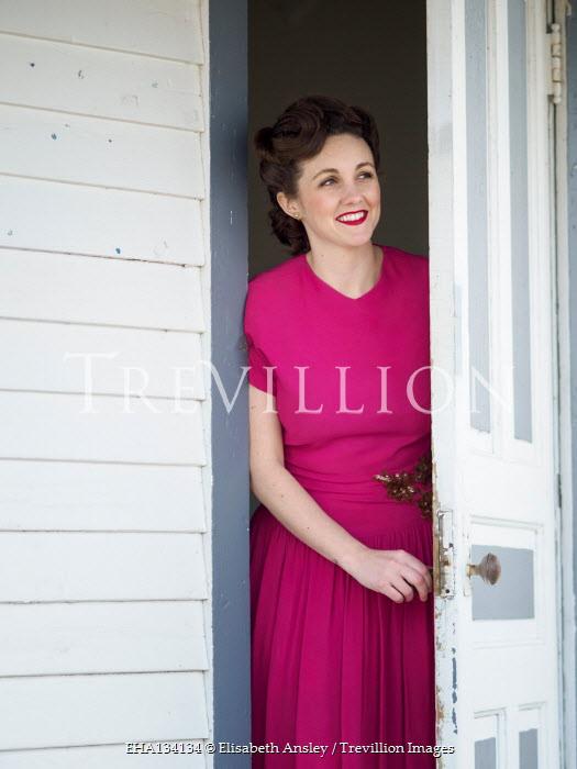 Elisabeth Ansley SMILING 1940S WOMAN IN DRESS OPENING DOOR